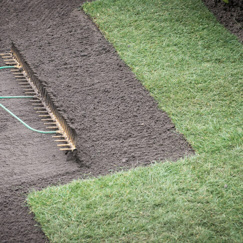 Preparing top soil and laying turf for new lawn
